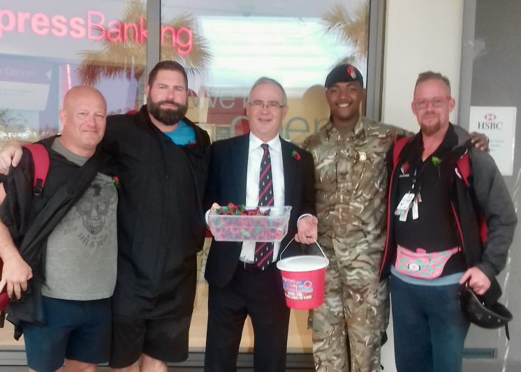 Governor John Rankin and Cpl Dante Durham sell poppies to members of the Canadian team in Bermuda for the World Rugby Classic. (Photograph by RBR)
